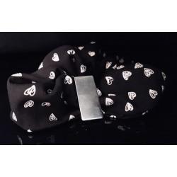 Scrunchie noir avec petit coeurs blancs et son bijou barrette sur un fond noir